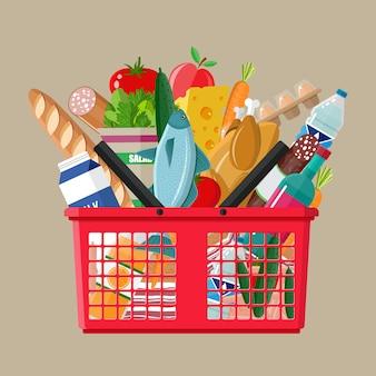 Carrinho de compras de plástico cheio de produtos de mercearia