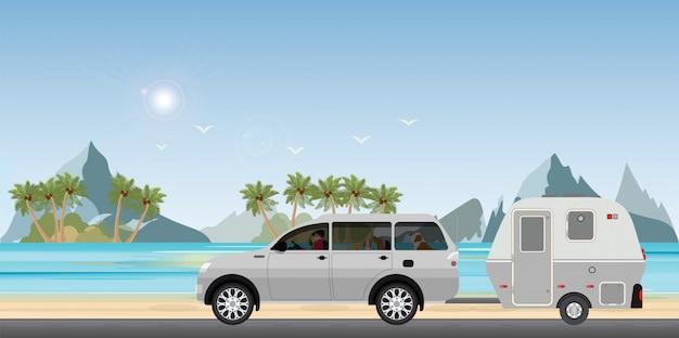 Carro da caravana que conduz o carro na estrada na praia.1