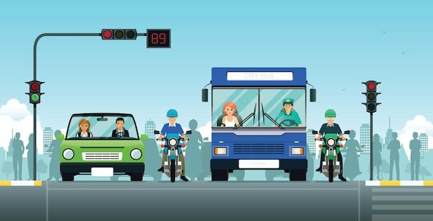 Carros e motocicletas aguardam o semáforo.