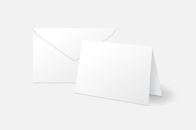 Cartão branco em pé e modelo de maquete de envelope isolado no fundo branco com sombra