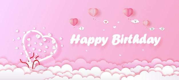Cartão de aniversário e coração de caixa de presente branco sobre fundo rosa.