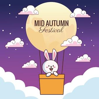 Cartão de celebração do meio do outono com coelhinho flutuando no ar quente do balão