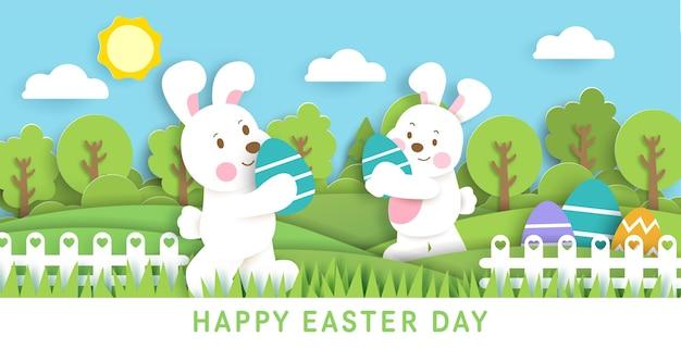 Cartão de dia de páscoa com coelhos fofos e ovos de páscoa