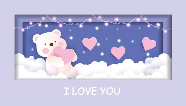 Cartão de dia dos namorados com fofo urso de pelúcia segurando um coração no estilo de corte de papel do céu.