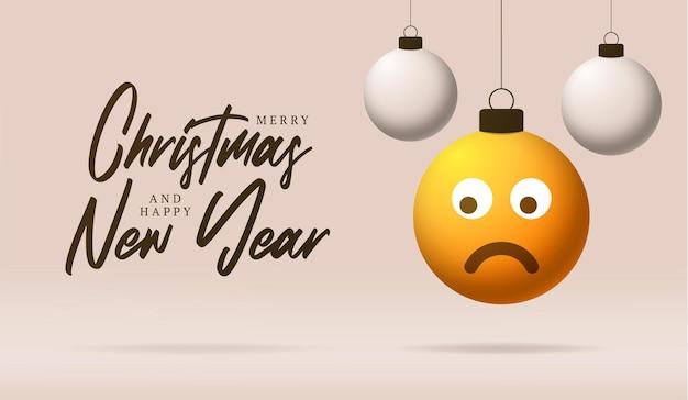 Cartão de feliz natal com cara de emoji triste. ilustração vetorial em estilo simples com letras de natal e emoção triste na bola de natal pendurada no fio do fundo