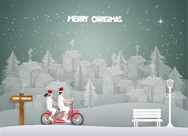 Cartão de feliz natal com casal andando de bicicleta vermelha na paisagem urbana branca e neve no inverno.