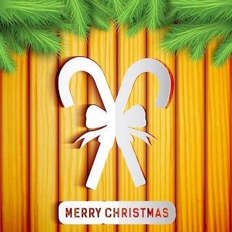 Cartão de feliz natal com silhueta de bastões de doces na parede de madeira com galhos de árvores de abeto