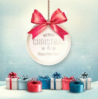 Cartão de feliz natal com uma fita e caixas de presente.