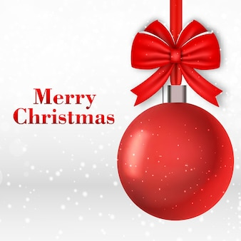Cartão de natal com bola vermelha em flocos de neve caindo