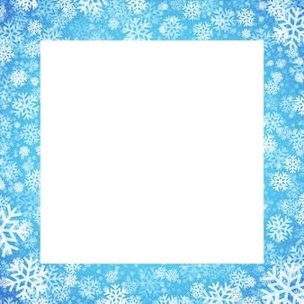 Cartão de natal com moldura de flocos de neve sobre fundo azul, cartão de felicitações