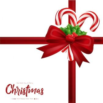 Cartão de presente de natal com laço vermelho, galhos de árvores de abeto e bastões de doces