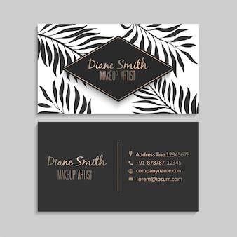 Cartão de visita escuro da obscuridade e do ouro com folhas tropicais