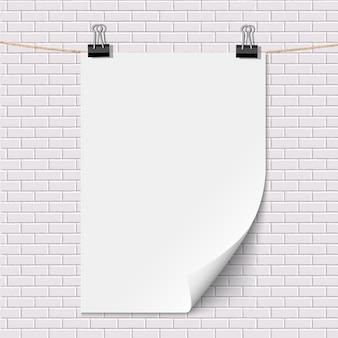 Cartaz de papel branco em branco pendurado na parede de tijolo branco