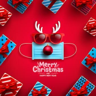 Cartaz ou banner de feliz natal e feliz ano novo com caixa de presente e símbolo de rena da máscara médica