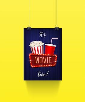 Cartaz pendurado em clipes de papel com balde de pipoca e copo de refrigerante com placa de filme