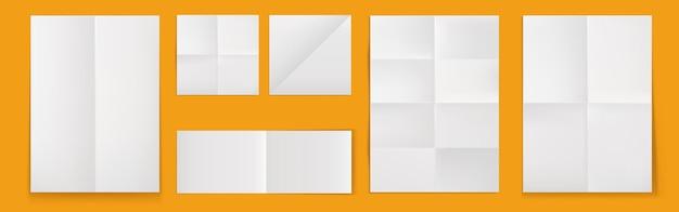 Cartazes dobrados em branco, folhas de papel branco com vincos cruzados