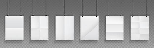 Cartazes dobrados em branco pendurados com clipes de pasta, folhas de papel branco com vincos cruzados e suportes.