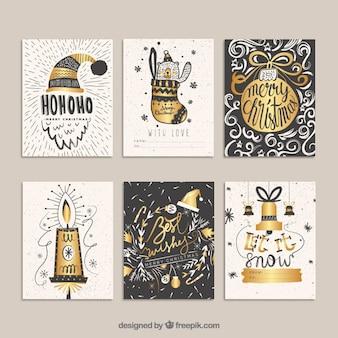 Cartões dourados do natal no estilo desenhado mão