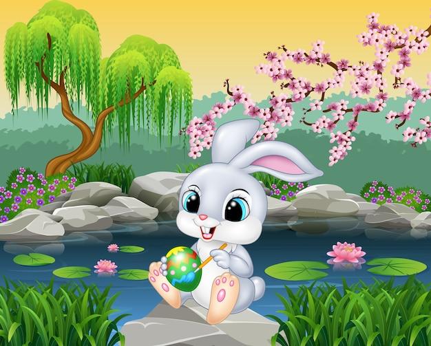 Carton feliz páscoa bunny pintando um ovo na rocha