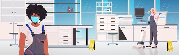 Casais de limpeza profissionais misturam zeladores usando equipamentos de limpeza trabalhando juntos no interior do laboratório médico horizontal