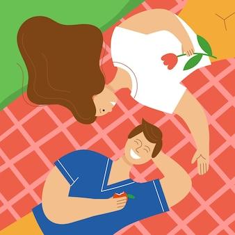 Casal apaixonado fazendo um piquenique no parque um homem e uma mulher deitados em uma manta e rindo