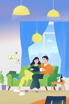 Casal apaixonado sentado em casa no sofá e assistindo filmes online