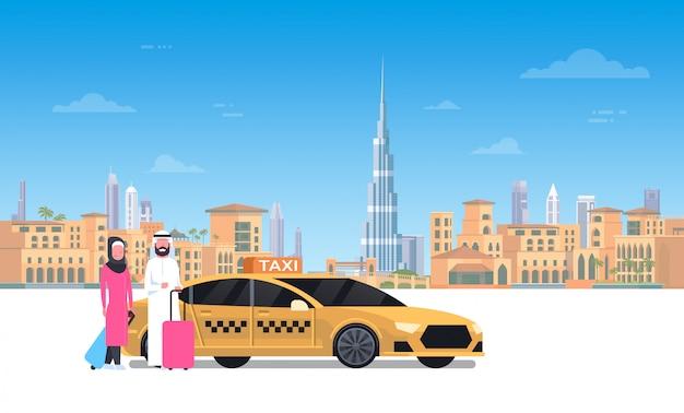 Casal árabe sentado no carro de táxi amarelo sobre a cidade de dubai
