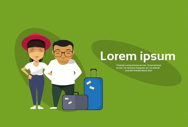 Casal asiático de viajantes ou turistas em pé com bagagem