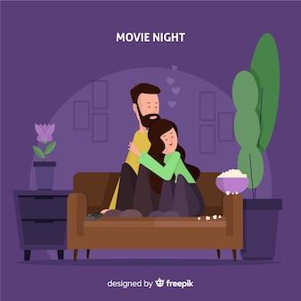 Casal bonito em uma noite de cinema abraçando no sofá