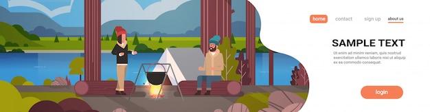 Casal, caminhantes, sentando, registro, homem, mulher, cozinhar, refeições, em, coco, fervendo, panela, em, fogueira, perto, acampamento, barraca acampamento, conceito, paisagem, natureza, rio, montanhas