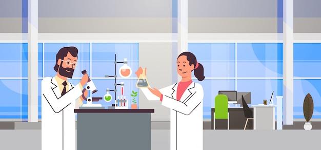 Casal cientistas trabalhando com microscópio no laboratório fazendo pesquisa homem mulher fazendo experimentos científicos médicos no laboratório interior retrato local de trabalho horizontal