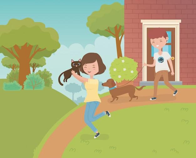 Casal com giro pequeno gato e cachorro no jardim da casa