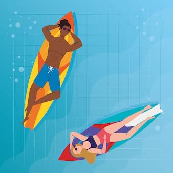 Casal com maiô, deitado em pranchas de surf, na piscina, temporada de férias de verão