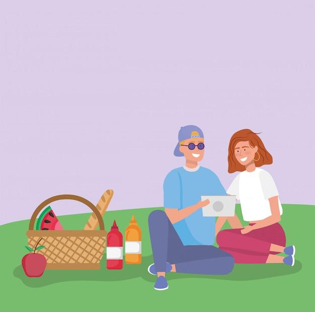 Casal com tablet com cesta comida grama piquenique