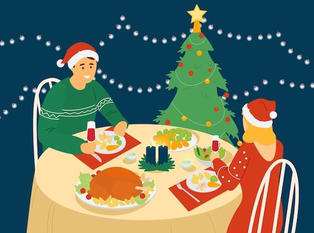 Casal comemorando o ano novo ou o natal, sentado à mesa com comida de natal.
