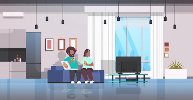 Casal comendo pizza homem mulher assistindo tv sentado no sofá conceito de fast-food saudável