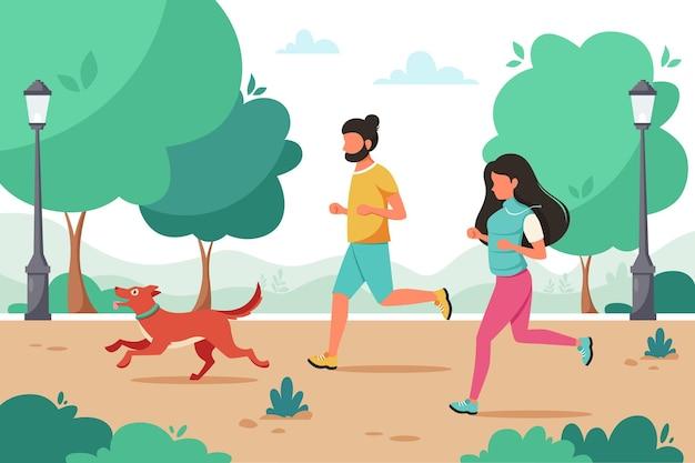 Casal correndo com o cachorro no parque. atividade ao ar livre