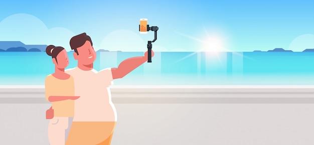 Casal dançando junto mar praia homem com mulher magra segurando selfie pau tirando foto