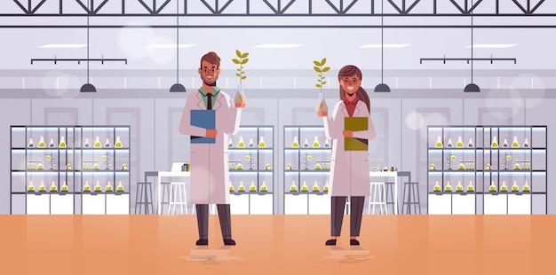 Casal de cientistas examinando amostras de plantas em tubos de ensaio