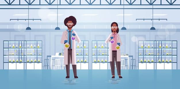 Casal de cientistas segurando tubos de ensaio com líquidos