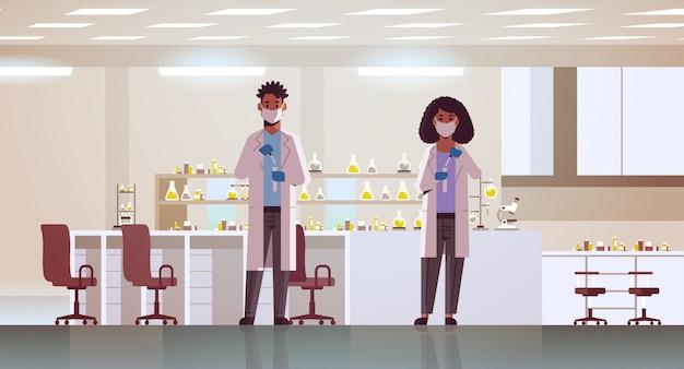Casal de cientistas segurando tubos de ensaio