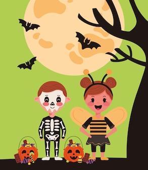 Casal de crianças pequenas com personagens de fantasias de halloween e morcegos voando