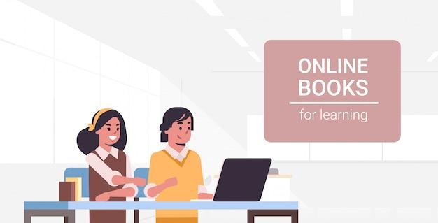 Casal de estudantes usando laptop menina e cara lendo livros on-line para aprender educação adolescente masculino feminino personagens de desenhos animados moderna sala de aula