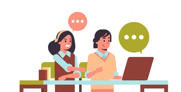Casal de estudantes usando laptop menina e cara sentado na mesa bate-papo bolha comunicação e-learning educação adolescente masculino feminino personagens de desenhos animados