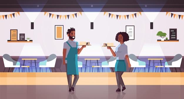 Casal de garçons carregando café e bolo na bandeja