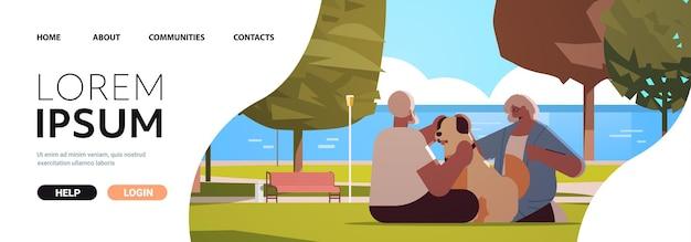 Casal de idosos passando um tempo com um cachorro em um parque urbano e relaxamento conceito de aposentadoria de corpo inteiro