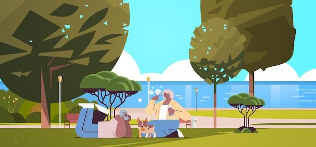 Casal de idosos soprando bolhas e passando um tempo com o cachorro no conceito de aposentadoria para relaxamento em parque urbano