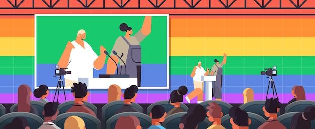 Casal de lésbicas discursando na tribuna em conferência que encontra pessoas transgênero e amam o conceito de comunidade lgbt