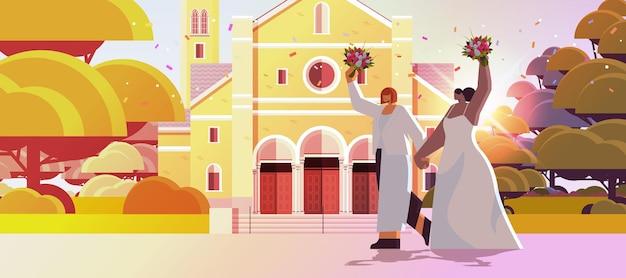 Casal de lésbicas recém-casadas com flores juntas perto de uma igreja transexuais amam a celebração de casamento na comunidade lgbt