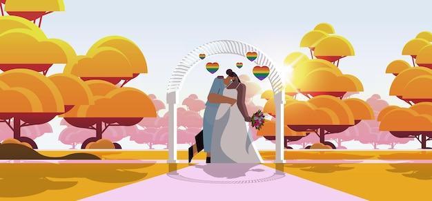 Casal de lésbicas recém-casado com flores se beijando perto de arco de casamento transgênero amor comunidade lgbt conceito de celebração de casamento horizontal ilustração vetorial de corpo inteiro